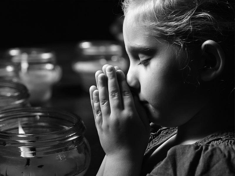 Girl Praying with Candles